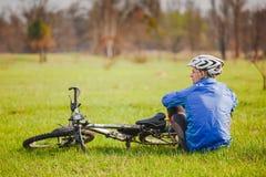 Cyklisten har en vila med cykeln Royaltyfria Foton