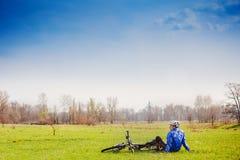 Cyklisten har en vila med cykeln Arkivbilder