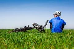 Cyklisten har en vila med cykeln på vårdag Arkivfoton