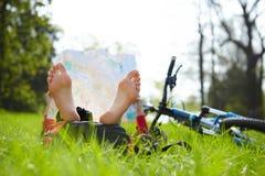 Cyklisten läser en översikt som barfota ligger på grönt gräs i sommar, parkerar utomhus Royaltyfri Foto