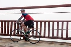Cyklisten med hjälmen rider över Golden gate bridge, San Francisco, CA arkivfoto