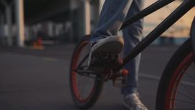 Cyklisten rider på hans bmx utomhus på solnedgången Ultrarapidnärbild lager videofilmer