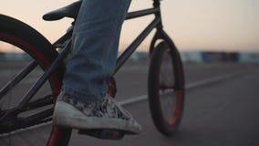 Cyklisten rider på hans bmx utomhus på solnedgången Ultrarapidnärbild stock video