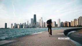 Cyklisten rider på sjösidan med skyskrapor på bakgrunden stock video
