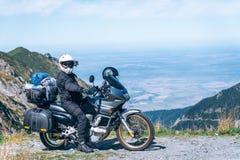 Cyklisten sitter på hans affärsföretagmotorcykel, det bästa berget i bakgrund, enduro, av vägen, den härliga sikten, faraväg in royaltyfri bild