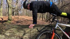 Cyklisten som att göra som är något, skjuter, ups på naturslingan som står bredvid cykeln stock video