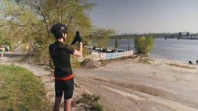Cyklisten som bär den svarta dräkten, hjälmen och solglasögon, rymmer hans mobiltelefonkamera och tar bilder av stadsfloden Manli stock video