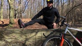 Cyklisten som värmer upp och gör som är någon, skjuter ups på naturslingan som står bredvid cykeln stock video