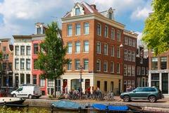 Cyklister och bil på en typisk genomskärning i Amsterdam Arkivbilder