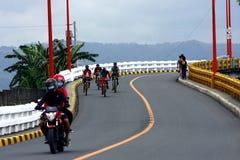 Cyklister och motorcykelryttare korsar den Tumana bron i den Marikina staden Royaltyfria Foton