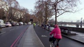 Cyklister rider i en upptagen cirkuleringsgränd i London vid Themsen bredvid vägtrafik arkivfilmer
