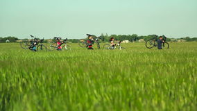 Cyklister som bär cyklar till och med högt gräs stock video