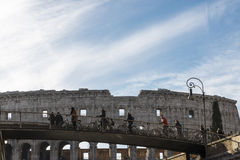 Cyklister som framme cirkulerar av coliseumen av Rome, Italien Arkivfoto