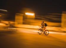 Cyklister som rider cyklar i en stad efter solnedgång Arkivfoto
