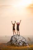 Cyklister som står på en stor sten nära mountainbiken fotografering för bildbyråer