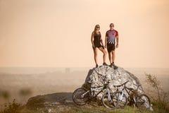 Cyklister som står på en stor sten nära mountainbiken Arkivfoto