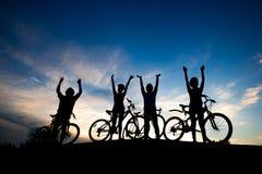 Cyklister som vilar på kullen på solnedgånghimmel fotografering för bildbyråer