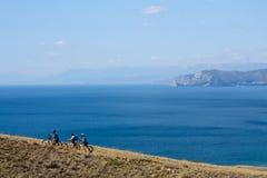 Cyklister stiger upp på montainen Arkivbilder