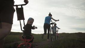 Cyklistfamiljkontur, f?r?ldrar med tv? ungar p? cyklar p? solnedg?ngen Begrepp av den v?nliga familjen lager videofilmer