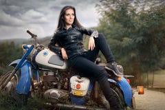 Cyklistflicka i läderomslag på den Retro motorcykeln royaltyfri fotografi