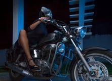 Cyklistflickan sitter på en avbrytarmotorcykel Royaltyfri Bild