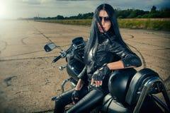 Cyklistflickasammanträde på en motorcykel Royaltyfria Bilder