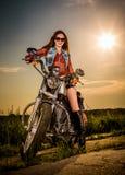 Cyklistflickasammanträde på motorcykeln arkivfoto