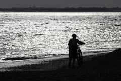 Cyklistkontur mot bakgrunden av skinande vatten Arkivbild