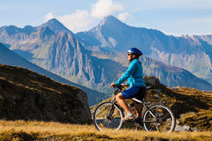 Cyklistkvinna i höjdmountais Arkivfoto