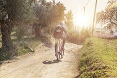 Cyklistperson på övande sportar för en cykel i naturen mot en solsignalljus Livsstil och aktivt begrepp med tomt kopieringsutrymm arkivfoto