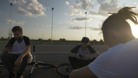 Cyklistpojkar som vilar, når att ha cyklat loppet som kontrollerar smartphones som håller ögonen på social massmedianätverksnyhet lager videofilmer