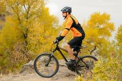 Cyklistridningcykel på den härliga Autumn Mountain Trail Arkivfoto