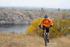 Cyklistridningcykel på den härliga Autumn Mountain Trail under floden Arkivfoton