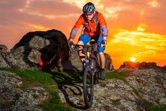 Cyklistridningmountainbiket fjädrar ner Rocky Hill på den härliga solnedgången Extremt sportar och affärsföretagbegrepp Royaltyfri Fotografi