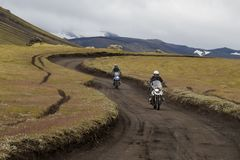 Cyklistritter på en grusväg bland bergen och de gröna kullarna royaltyfri bild