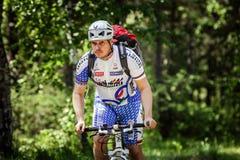 Cyklistritter till och med skogen Arkivfoto
