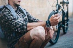 Cyklistsammanträde för ung man bredvid cykeln och hans seende Smartphone Stads- dagligt begrepp för gatalivsstil Royaltyfri Foto