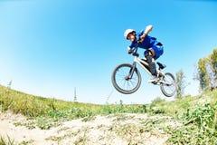 Cyklisty jeździecki doskakiwanie z rowerowy przez cały kraj Zdjęcie Stock