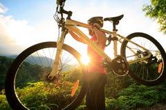 Cyklisty przewożenia rower górski na wschodu słońca śladzie Obrazy Stock