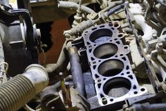 The cylinder block of the four-cylinder engine. Disassembled mot. Or vehicle for repair. Parts in engine oil. Car engine repair in the service Stock Photography