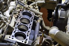 The cylinder block of the four-cylinder engine. Disassembled mot. Or vehicle for repair. Parts in engine oil. Car engine repair in the service Stock Image