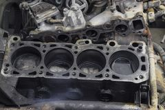 The cylinder block of the four-cylinder engine. Disassembled mot. Or vehicle for repair. Parts in engine oil. Car engine repair in the service Stock Photos
