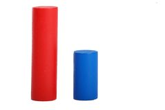 Cylinders as a diagramme. Studio shot of simple diagramme of two red and blue wooden cylinders of different sizes on business concept theme Royalty Free Stock Photos