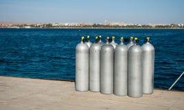 Cylindrar med helium på skeppsdocka tio vita cylindrar för dykare på havsskeppsdocka syrebehållare för dykare på pir Royaltyfri Bild