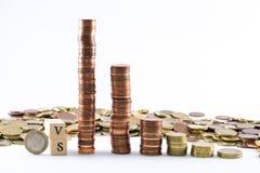 Cylindres d'euro pièces de monnaie et les lettres contre formé par de petits cubes en bois Image stock
