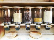 Cylindrical Bulk Grains and Beans Dispenser. A European quality health food bulk foods section with a variety of grains and royalty free stock photos