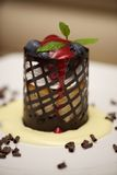 Cylindrical cheesecake in chocolate basket with blueberries Royalty Free Stock Image