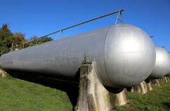 Cylindrical tanks of an industrial plant for the storage. Giant cylindrical tanks of an industrial plant for the storage of methane gas for the supply of energy Royalty Free Stock Photo