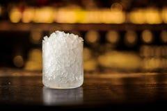 Cylindriskt coctailexponeringsglas av krossad is som står på stångräknaren royaltyfri bild