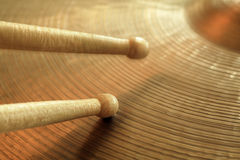 Cymbal and drumsticks. Photo of two drumsticks playing on a hi-hat or ride cymbal.  Focus on tip of lower stick while other stick has slight motion Royalty Free Stock Photos